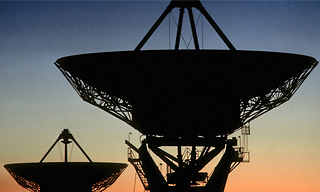 Two radio telescopes photographed against the dawn sky